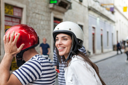 Young couple riding moped through village, Split, Dalmatia, Croatia