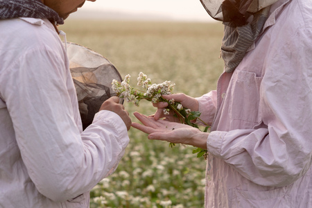 Cropped shot of male and female beekeepers inspecting plant in flower field, Ural, Russia LANG_EVOIMAGES