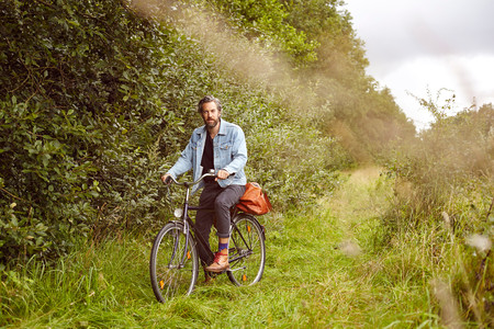 Portrait of mid adult man on bicycle on rural path