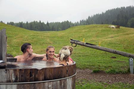 Four adult friends relaxing in rural hot tub, Sattelbergalm, Tyrol, Austria