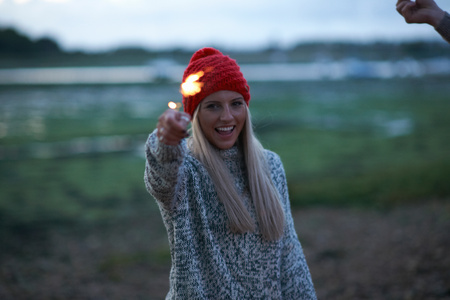 Portrait of young woman playing with sparklers near sea at dusk
