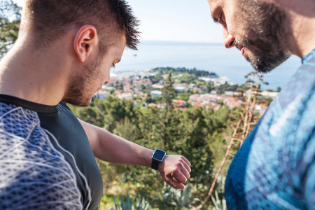 Two male runners checking smartwatch in park, Split, Dalmatia, Croatia