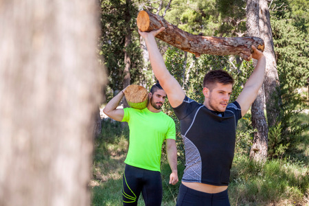 Two young men doing weightlifting training with logs in forest, Split, Dalmatia, Croatia
