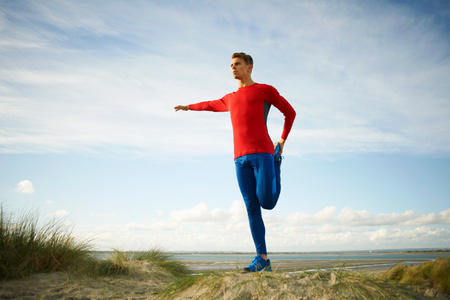 Man on sand dune standing on one leg doing stretching exercises