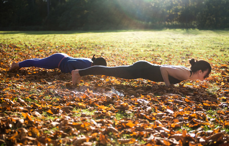 aspirational: Two women doing yoga in park on autumn day LANG_EVOIMAGES