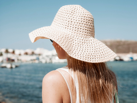 focus on foreground: Rear view of woman wearing sun hat, Menorca, Spain LANG_EVOIMAGES