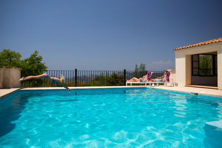 Young woman diving into boutique hotel swimming pool, Majorca, Spain