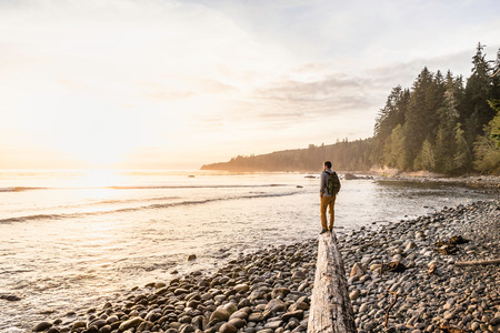 Man looking out from driftwood log on beach in Juan de Fuca Provincial Park, Vancouver Island, British Columbia, Canada
