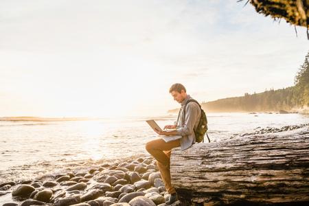 Man sitting using laptop on beach in Juan de Fuca Provincial Park, Vancouver Island, British Columbia, Canada