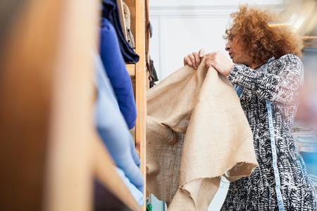 Owner of small fashion business working in material storeroom
