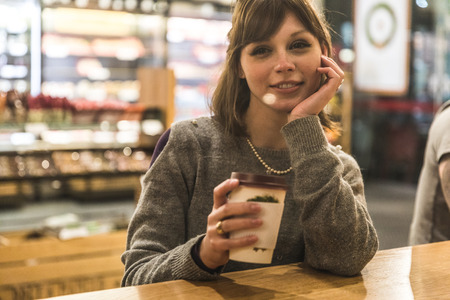Portrait of young woman sitting in coffee shop, holding coffee cup