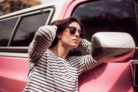 leaning against: Young woman with hands in long brown hair looking at vehicle wing mirror LANG_EVOIMAGES