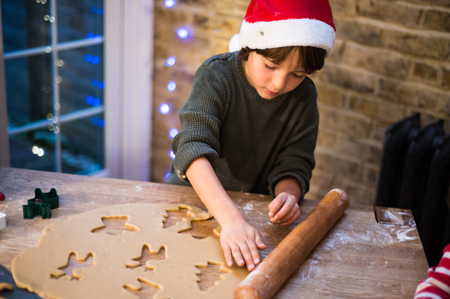 Boy in Santa hat preparing Christmas cookies at kitchen counter