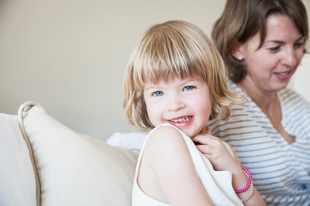 3 4 years: Portrait of cute girl sitting up on bed with mother