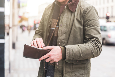 Man checking wallet in front of shop, London, UK