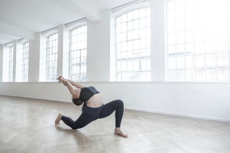 Woman in dance studio bending backwards stretching