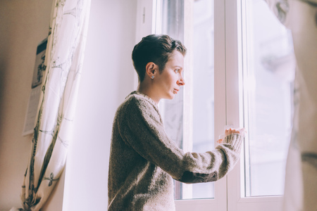Portrait of young woman staring through window at home