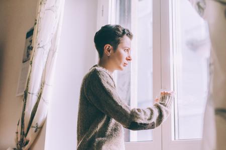 Portret gapi się przez okno w domu młoda kobieta LANG_EVOIMAGES