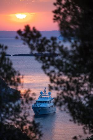 Yacht anchored off coast at sunset, Calvia, Majorca, Spain LANG_EVOIMAGES