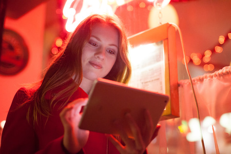 Young woman using digital tablet in neon signage shop, London, UK
