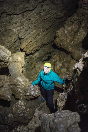 Woman in cave, Horne Lake Caves Provincial Park, Vancouver Island, British Columbia, Canada