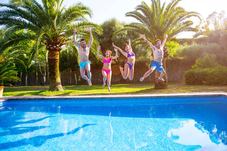 in unison: Friends jumping in swimming pool