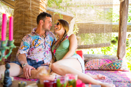 Couple sitting together in pergola face to face smiling