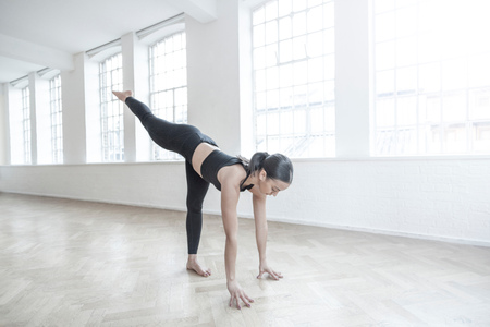 spandex: Woman in dance studio bending forwards stretching