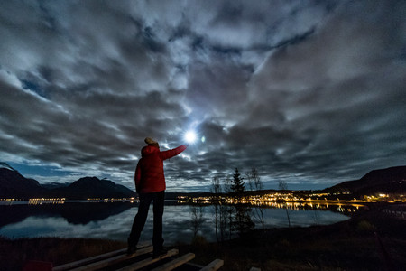Woman with torch near Tromso in autumn, Arctic Norway