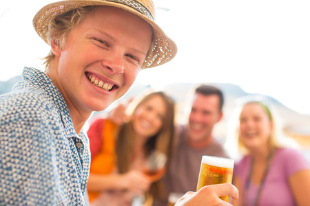 Portrait of young man with adult friends at waterfront restaurant, Majorca, Spain