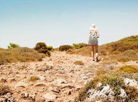 Rear view of woman carrying beach bag, Menorca, Spain