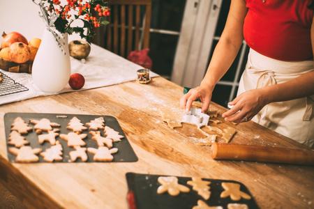 W połowie sekcja kobiety ciie Bożenarodzeniowych ciastko kształtuje przy kuchennym kontuarem LANG_EVOIMAGES