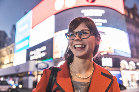Young woman standing in front of illuminated billboards, smiling LANG_EVOIMAGES