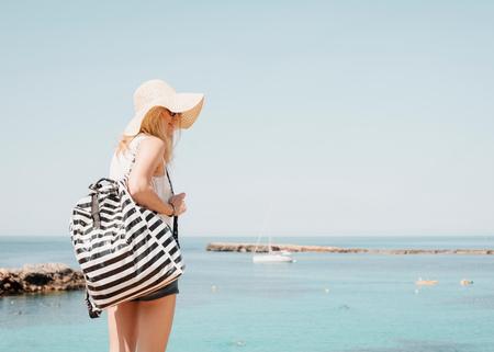 Woman by sea wearing sunhat, Ciutadella, Menorca, Spain