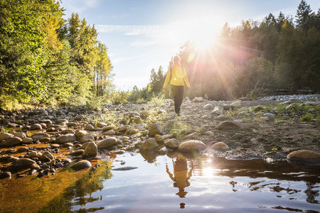 Female hiker walking on riverbed in Englishman River Falls Provincial Park, Vancouver Island, British Columbia, Canada