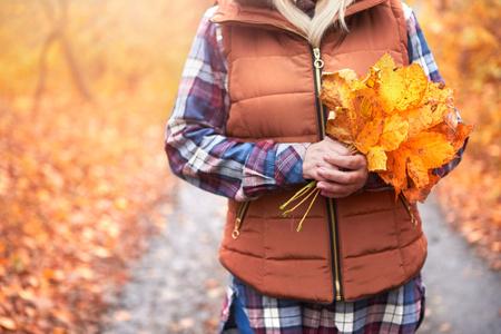 Kobieta stoi na zewnątrz, trzymając jesienne liście, w połowie sekcji