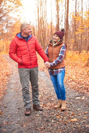 Starsza para spaceru wzdłuż drogi wiejskiej, jesienią