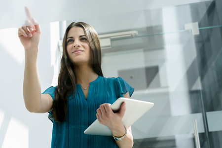 Young businesswoman finger writing on window at office entrance LANG_EVOIMAGES
