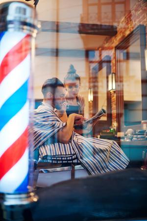 Hairdresser showing customer magazine