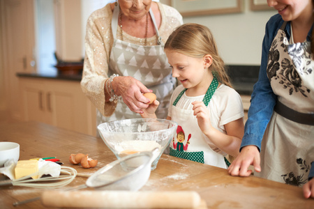 Senior woman and granddaughters cracking eggs for cookies