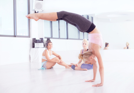 Young female ballet dancer practicing in dance studio,doing handstand