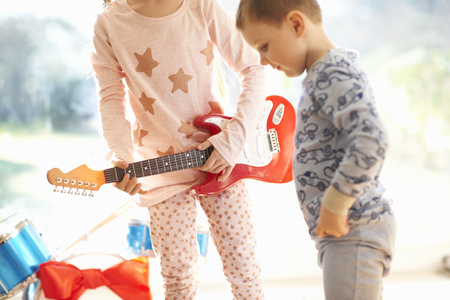 nightwear: Girl and brother playing with toy guitar on christmas day