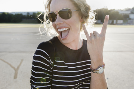 Portrait of mid adult woman wearing sunglasses making hand gesture