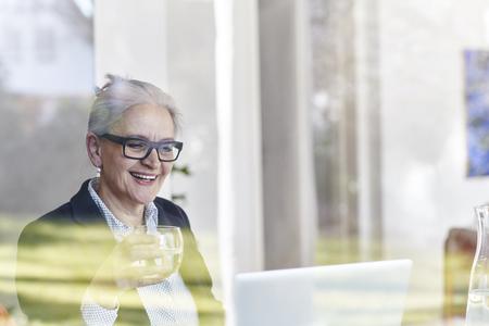 Vista de la ventana de inicio de la empresaria senior mirando portátil