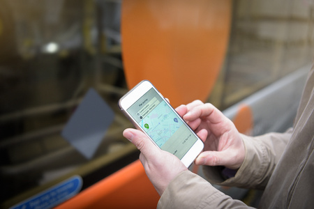 Passenger using smart phone to look at bus timetable before boarding electric bus