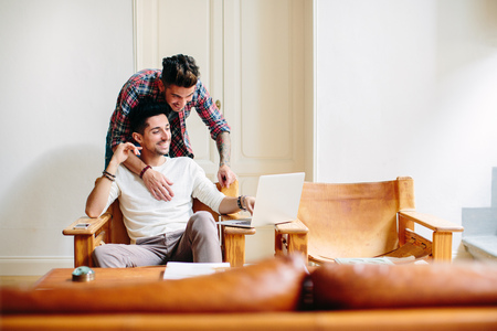 age 25 30 years: Young man at home,sitting in chair,using laptop,his partner hugging him from behind