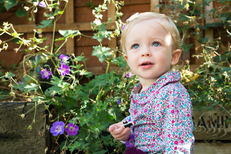 Blue eyed baby girl looking up in garden