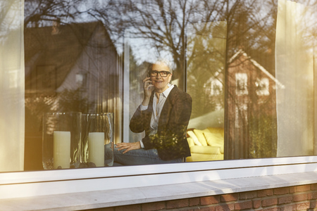 aging woman: Home window view of senior businesswoman making smartphone call LANG_EVOIMAGES
