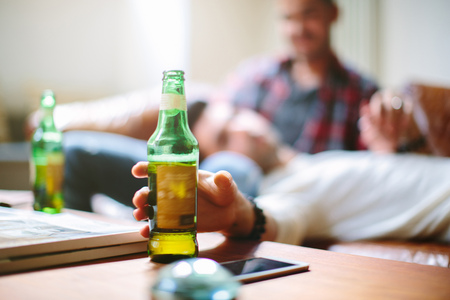 age 25 30 years: Male couple relaxing on sofa,man reaching for beer bottle LANG_EVOIMAGES