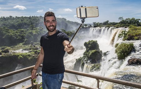 Man posing,taking a selfie in front of Iguazu falls,Misiones,Argentina